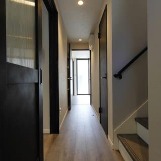 玄関の奥のプライベート動線は、来客中にお子さんが帰宅しても顔を合わせず、気兼ねなく2階へと上がれる。奥に見える明るいスペースは洗面室