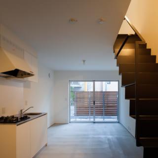 叔父さま世帯の1階LDKは前庭と同じモルタルの床。前庭との一体感が増し、屋外とつながる心地よさがある