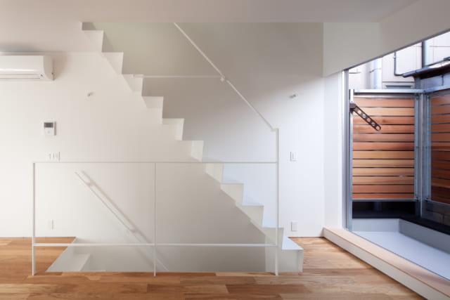 Yさま世帯の室内階段。叔父さま世帯の黒い階段とデザインをそろえ、色はホワイトにしている。見た目が軽やかで、空間を広く感じる効果も。洗練されたデザインの階段があると、インテリアの質が上がる