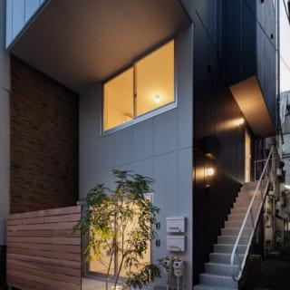 1、2階は奥に寄せて前庭をつくり道路との距離を確保。緑の彩りと壁から跳ね出した外階段で洒落た佇まいに