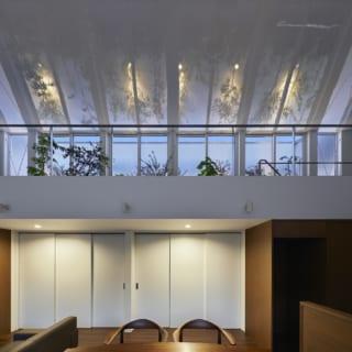 夜間は、日中と同様に上からそそぐ光で家全体が明るくなるように照明をプランニング。写真は2階テラスの照明と、1階の照明の一部をつけた状態。照明は各所に分散して設置し、それぞれの照明のオン・オフで好みの明るさになるよう配慮している