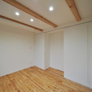 1階の奥さまの個室。床は奥さまセレクトのサクラの木。写真中央の凹んだ部分は、和装がお好きな奥さまの桐ダンスのサイズに合わせている。その横の引き戸の先は大容量のウォークインクローゼット