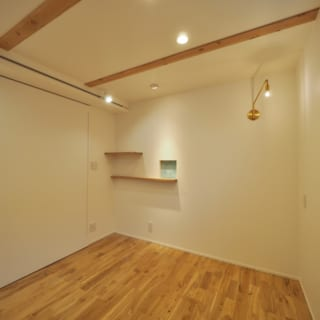1階のMさまの個室は、天井の梁を出して表情をつけた。写真右の照明はMさまのセレクト。吉田さんはこの照明とのバランスを考え、写真左上部にさりげなくレール照明を設置。写真奥の小さな曇りガラスの窓は玄関のニッチ棚とつながっていて、ほのかに明かりが漏れて気配がわかる