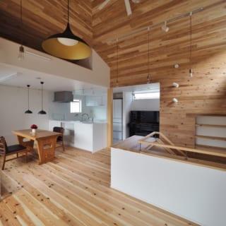 2階LDK。手前のリビングは天井も壁も板張り。高い天井は3方向に勾配がついており、のびやかな開放感を生んでいる。対して、奥のキッチン・ダイニングは天井高を抑えて白壁とし、間仕切りを設けずに空間を分けている。ダイニング上部には左の梯子でのぼる収納スペースも