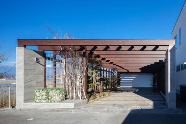 自邸玄関に続くパーゴラのアプローチは青空と植栽に彩られ、リゾート感たっぷり。いきなり玄関があるのではなく、住まいへの序章ともいえるこうした空間を経ると気持ちが和らぎ、オン・オフを自然に切り替えることができる