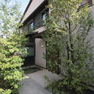 玄関へのアプローチ。建物をL字に凹ませてできた余白を前庭にすることで、旗竿地でもゆとりを感じる造りに