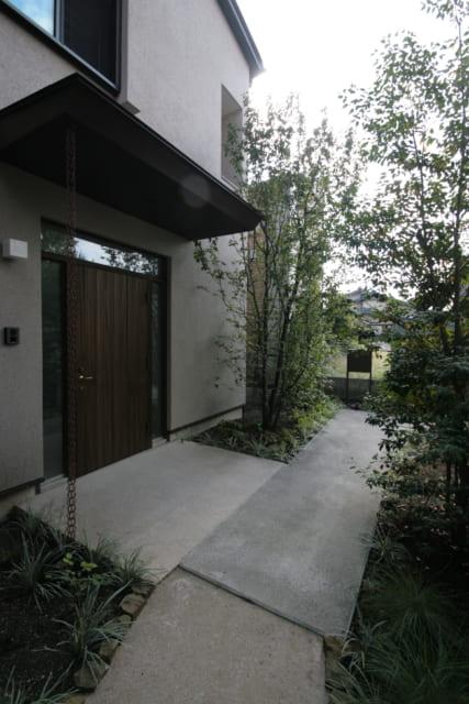 玄関前から路地方面を見る。H邸の窓はいずれも、庭木の緑が見える「ちょうどよい場所」につくられている
