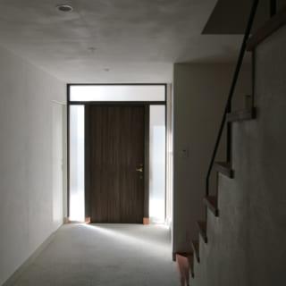 1階ギャラリーの床はモルタルの洗い出し仕上げ、壁は珪藻土の左官塗り。玄関から入る細い光で質感が際立つ