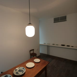 1階応接間はディスプレー棚が豊富。壁向こうのスリット窓からは、自然光が間接照明のようにほんわりと入る