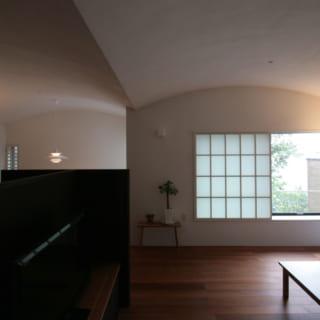 2階。右がリビング、左奥がダイニング。連続するカーブ天井が、たゆたう波や教会のアーチ天井を思わせる