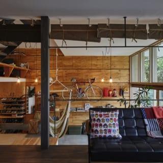 リビングから土間を見る。ミッドセンチュリーテイストの家具とインダストリアルな土間の雰囲気がよく合い、洒落た雰囲気。一体感がありつつも、床の高さの違いによって、それぞれの空間の適度な独立感もキープされている