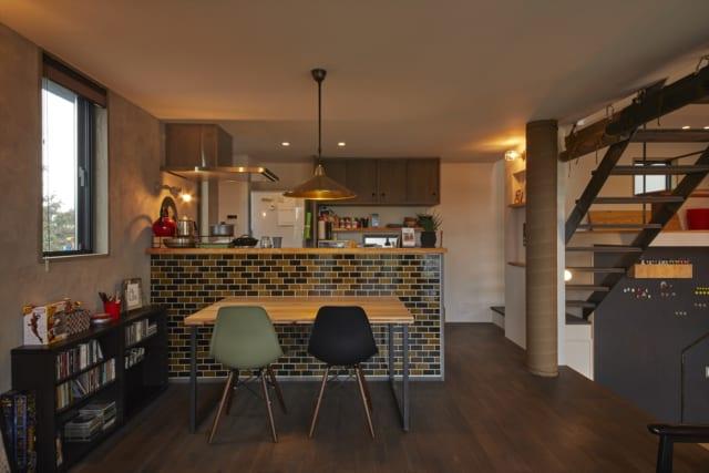 ダイニング&キッチン。モザイクタイルがレトロな雰囲気を醸すキッチンカウンターは、手元が見えないよう高めに設置。床は濃いブラウンで塗装したオーク材。壁は天然素材のペンキ塗装。自然素材の質感が活きる内装で、ホッと落ち着ける空間になった