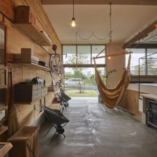 土間の奥から玄関を見る。土間は1階の約半分ものスペースを取っており、Tさま所有の豊富なアウトドアグッズを「普段使いの道具」として置くことができる。板張りの壁(写真左)は棚板を自由に抜き差しできる造りで、お気に入りのアイテムを思い通りにディスプレー可能