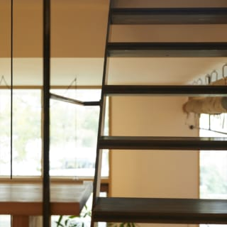 2階への階段は、蹴込(けこみ)のないオープンなデザイン。土間や屋外の景色を見ながらの移動が楽しい