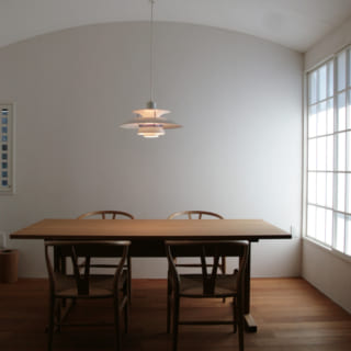 2階ダイニング。ルイスポールセンの照明や、シェーカー家具をモチーフにしたダイニングセットがよく映える