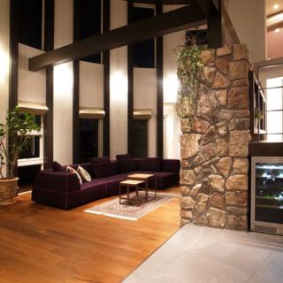 夜の1階リビングは、リゾートホテルのような高級感と穏やかなくつろぎに満ちている。柱や梁など、垂直・水平の木材を入れることで空間が引き締まり、広くても守られているような心地よさがある