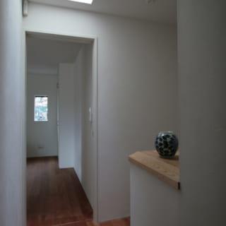 2階の主寝室や子ども室へ向かう通路。天窓の下の角に棚があり、ここにもアートをディスプレーできる
