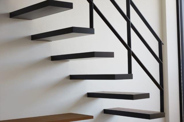 2階への階段は、浮遊感のある片持ち階段。一般的に木造で片持ち階段を設置するのは難しく、さらにこれだけ踏み板を薄くするのも高難度。大塚さんは緻密な構造計算を行ったほか、踏み板の材質にこだわり、壁の中に鉄板を入れるなどの工夫を凝らして実現した