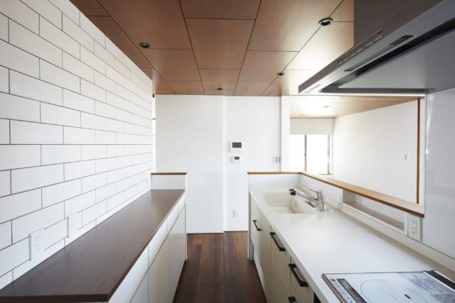 奥さまこだわりの、グレー目地のタイル壁がかわいいキッチン。カウンターの腰壁はリビング・ダイニングから手元が見えない高さで、調味料などを置けるニッチ収納もあって使い勝手がよい。天井はシナ合板だが塗装や目地のある張り方で、コストを抑えつつ高級感をアップ