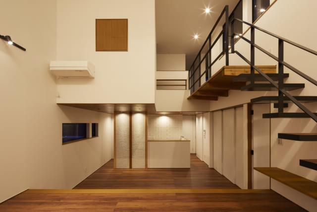 1階リビングからダイニング、キッチンを見る。リビングは吹抜けだが、ダイニングは上に2階の一部を配して天井高を抑え、落ち着きのある空間に。大塚さんが構造計算で試行錯誤したおかげで支えの柱がない無柱空間を実現でき、空中に部屋が浮いたように見え、開放感を高めている
