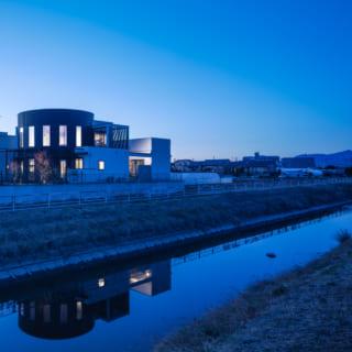 F邸の敷地は道路と川の間にあり、仕事場は道路側、住まいは川側に配置されている。川から見るF邸は洗練された円形の佇まいが美しく、水辺のリゾートホテルを思わせる