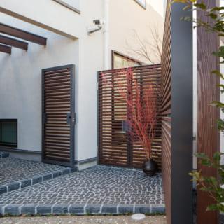 パーゴラのアプローチの先には、ルーバーと石畳で仕上げられた玄関ポーチが。ここで写真左手に折れて玄関扉にたどり着く動線が、くつろぎの自邸への期待を高める