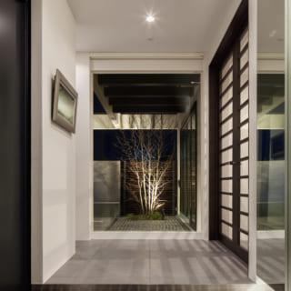 玄関の正面には中庭が見え、視線の抜けと癒しの緑が心を落ち着かせる。写真右手の両開きドアの先がLDK