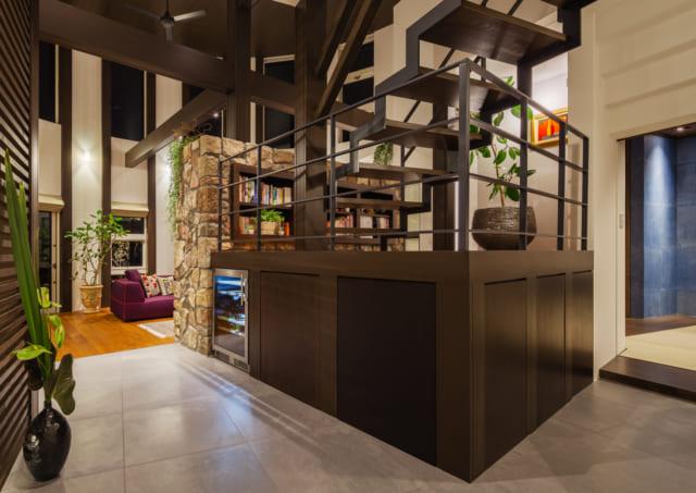 1階LDKの中央に位置する中2階。写真奥のリビング側は石壁で仕切られているが、ほかの面は壁がなく、家族の気配もわかるほどよい「こもり感」が魅力。ワインが好きなご夫妻のために、段差を活かしてワインセラーも設置した