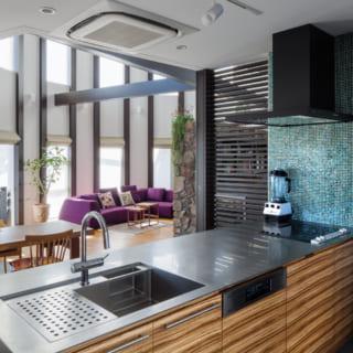 1階キッチンからの眺め。ダイニングだけでなく円形の吹抜けリビングも見通せて、青空や屋外の景色を眺めながら料理ができる