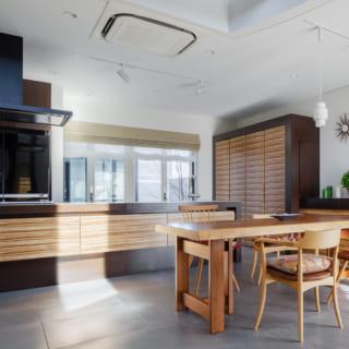1階キッチン&ダイニング。キッチンカウンターの腰壁は、上部を手前に倒してテーブルにすることもできる。キッチンの奥に見えているのは邸内に複数ある中庭の1つ。その先にはゴルフ練習スペースがある