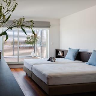 2階主寝室。テラスの先には川、左には1階中庭の植樹が見える。朝日にきらめく水面と緑が視界に入る目覚めは、リゾートの朝そのもの