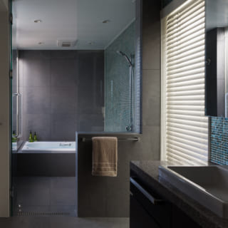 水まわりは1階。写真奥のバスルームの左手には専用の中庭があり、緑を眺めて入浴できる。洗面スペースにはキッチンと同じグリーン系のタイルを使用。「Fさまの前のお住まいにグリーンのカーテンがかかっていたので、お好きなのかなと思ってご提案しました」と金子さん