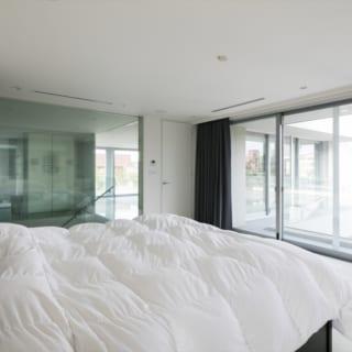 3階主寝室。奥の階段側と右のテラス側はガラスで見通しがよく、気持ちのよい光が入る