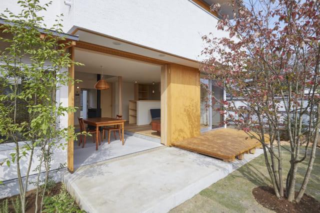 南の庭から邸内を見る。土間のダイニングの先は土間テラス、スギ床のリビングの先はウッドデッキ。邸内から外に向かって同じ素材の床が連続することで、内と外の一体感が増し、開放感もアップ