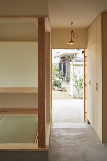 土間の玄関ホールから玄関を見る。土間はダイニングまでL字でつながる。写真左は玄関脇のゲストルーム