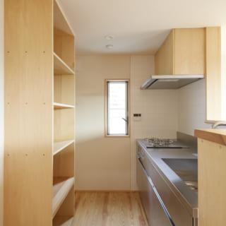 オールステンレスの1階キッチン。左の食器棚は造作。奥に施主さまの手もちの家具が入るように設計した