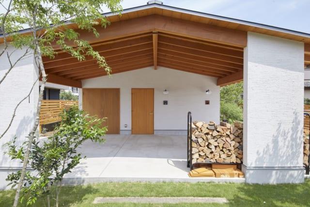 西から見たS邸外観。玄関は西にあり、ポーチは車寄せとして使える贅沢な広さ。ストーブ用の薪を雨にぬれずに置いておけるよう、屋根も大きく取ってある。あらわし仕上げの屋根の構造材は、ピーラー(木目が細く美しい良質なベイマツ)を使用