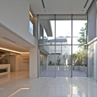 1階リビングからダイニング(左奥)、テラス(正面)を見る。空まで見える吹抜けと全面ガラスの効果で広いテラスと一体化し、心地よい開放感を味わえる