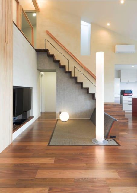 玄関扉を開けた瞬間に広がる、ひとつ屋根の吹抜空間。リビングはフローリングと同面のカーペット敷きで、空間がより高く広く感じられる。階段の壁面のスリットからは、トップライトからの光が間接光となって溢れ出る。