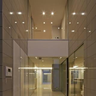 高級感漂う吹抜けのエントランスホール。ガラスが多用され、2階のホールや右手のキッチンも見通せる