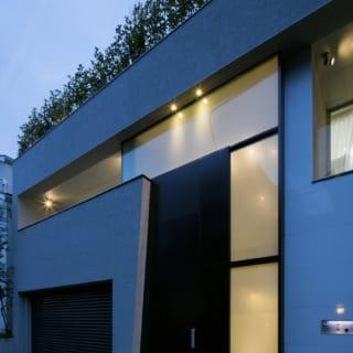 ドアの外枠のシャープなデザインが目を引く外観。上部のガラス越しに吹抜けの邸内の開放感がうかがえる