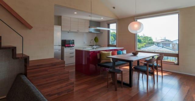 料理の時間も楽しく使いやすく。シンクを備えたアイランドキッチンはビビットな配色で吹抜側に、調理や収納スペースは壁側に。「使い勝手と機能配置を何度も考え合いました」と明美さん。