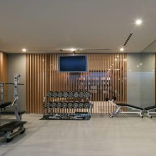地階トレーニングジムからファミリーラウンジを見る。この2室はルーバースクリーンで仕切られ、施主さまがトレーニング中もラウンジで遊ぶお子さまたちの様子がわかる