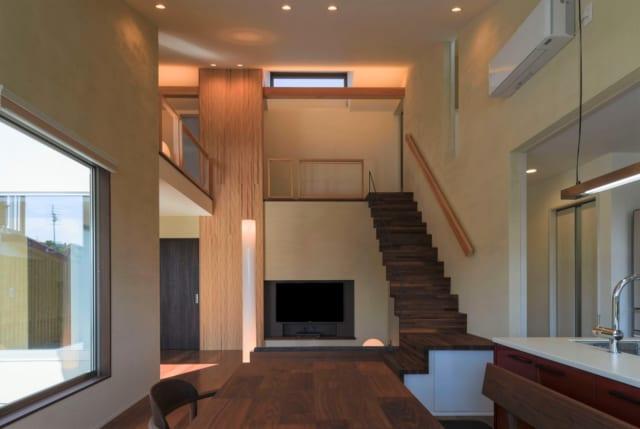 1階と2階がひとつになったオープンなパブリックゾーン。開閉可能な高窓を吹抜上部に設けたことで、北側からの安定した自然採光と南北の通風換気ができ、いつも明るく心地よい。寝室などのプライベートゾーンは、階段の右の壁の向こう。自然な動線で行き来できる。