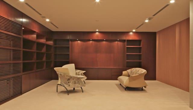 地階のファミリーラウンジ。正面中央にスクリーンを入れ、シアタールームとしても使える。内装はあめ色の天然木が用いられ、1階のモダンな建築とはまた違うクラシカルな上質感が漂う