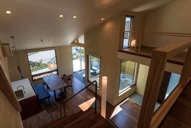2階から見下ろす。外部(テラスと中庭)と内部(テラスリビングとエントランス、2階)が立体的に繋がりあうプランは、面積以上に空間の拡がりが感じられ、どこにいても自然の光と風を享受できる。