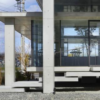 駐車場からエントランスを見る。宙に浮いたような階段が軽やかな印象を与えている。一番低い位置の屋根が大きく外に出ることで庇のような役割を果たしている。程よく太陽光を遮るため、客席では眩しさを感じない