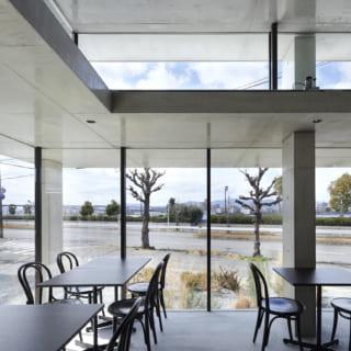 客席は、天井が低い部分に配置。天井高を抑えることで落ち着いた空間になり、お茶や食事をゆったりと楽しむことができる。ダウンライトは、明るいうちはその存在に気が付かないほどごく控えめに設置した。窓の外には海が見え、ずっとここにいたいと感じる空間になった