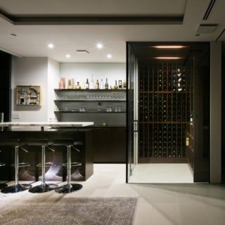 1階バーカウンター。手前のダイニング、左手のリビング、右手のキッチンの中央に位置し、ゲストがさまざまなスペースを行き来する欧米のパーティースタイルにぴったりのレイアウト。ガラス張りのウォークインワインセラーの中には200本以上のワインがずらり