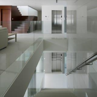 2階から1階への階段(手前)と3階への階段(奥)を一望するこの場所は、上質なモダン建築のお手本のようなスポット。手すり壁の強化ガラスは、支えの部材が見えない高度な設計。余計なものをそぎ落とした透明感あふれる空間が、階段や床の造形美を際立たせている